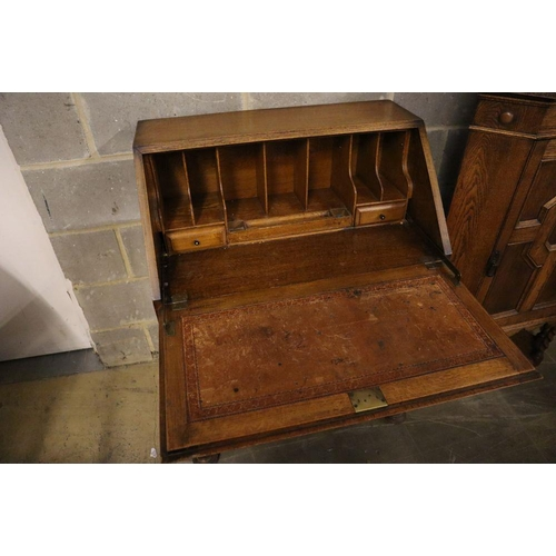52 - <B>A 1920's panelled oak bureau, width 74cm, depth 46cm, height 103cm, together with a similar stand...