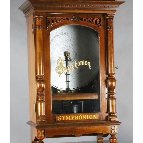 35 - <B>A late 19th century German walnut cased upright Symphonion,</b></i> with lyre shaped pediment, pi...