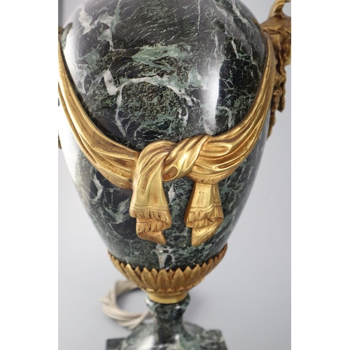 51 - <B>A pair of early 20th century ormolu green marble table lamps,</b></i> with ovular form with mask ...
