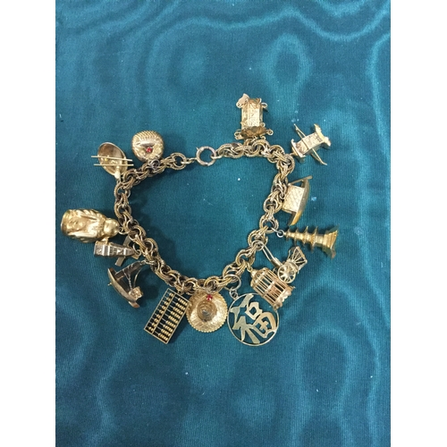 12 - A vintage 14ct gold fancy link bracelet, suspending an array of charms -...