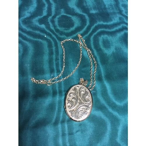 21 - A large 9ct gold locket, oval, with scrolled cover, to 9ct chain -...