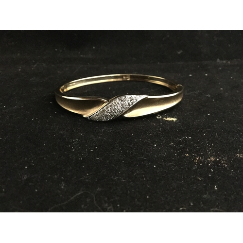 50 - A yellow gold hinged bangle,  pave set with a panel of diamonds -...