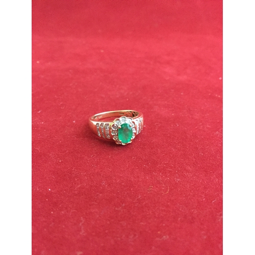 27 - An emerald and diamond dress ring,  with oval emerald in diamond border and stepped shoulders, to 14...
