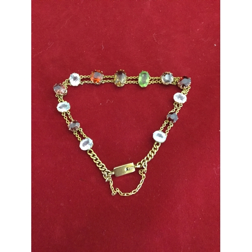 31 - An early 20th century multigem set bracelet,  composed of graduated oval semi-precious stones betwee...