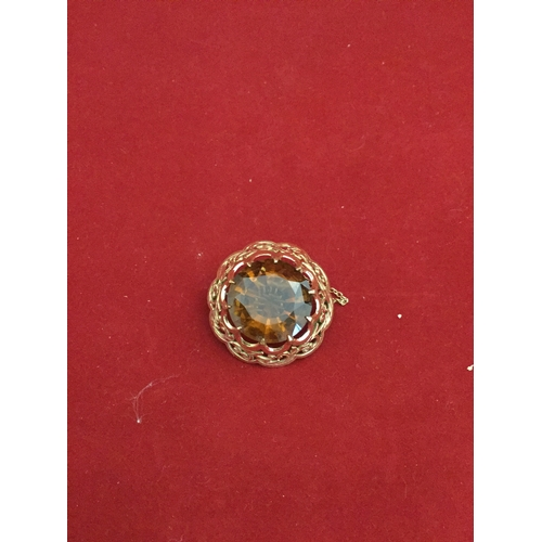 44 - A citrine brooch,  the large circular stone set in engraved and pierced yellow metal mount -...