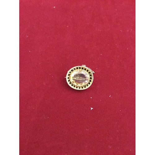 47 - A citrine set brooch,  the oval citrine in pierced and rope twist frame -...