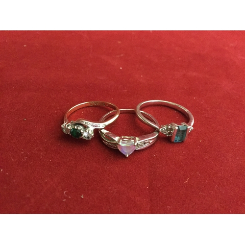 59 - A group of three 9ct gold rings,  including a blue topaz and diamond set cluster -...