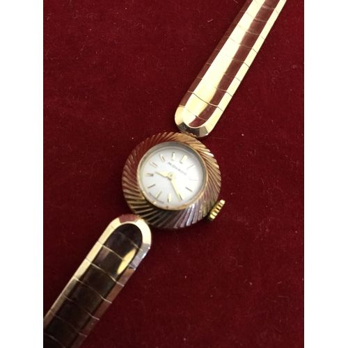 5 - A lady's 9ct gold wristwatch by Movado,  the signed circular dial to 9ct bracelet strap -...