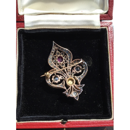 48 - A late 19th century diamond, ruby and pearl brooch,  of open fleur de lys form, with a central oval ...
