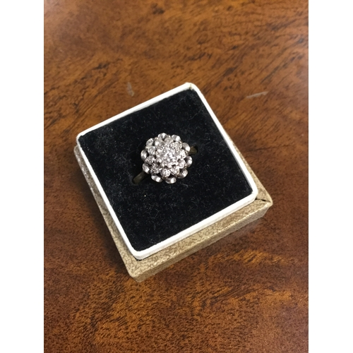 13 - An 18ct gold diamond set ring,  the central diamond in a flowerhead cluster to button style back and...