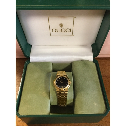 30 - A lady's wristwatch, signed Gucci,  with black dial and gold plated bracelet strap, boxed -...