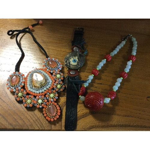 31 - A modern wristwatch, the case decorated with native American style detail, a stone set bib style nec...