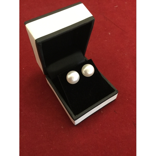 47 - A pair of cultured pearl ear-studs, each on silver posts -...