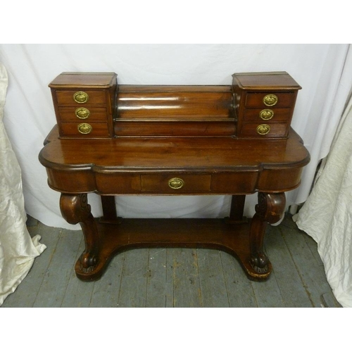 11 - A Victorian mahogany desk shaped rectangular on scrolling legs with brass handles to seven drawers o...