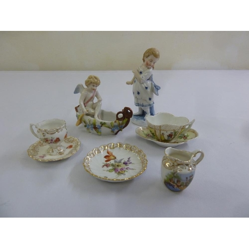 125 - A quantity of porcelain to include two figurines and miniature cabinet cups and saucers (8)...