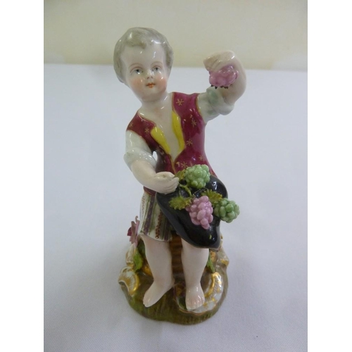 136 - A Continental figurine of a boy eating grapes, marks to the base, 11.7cm (h)...