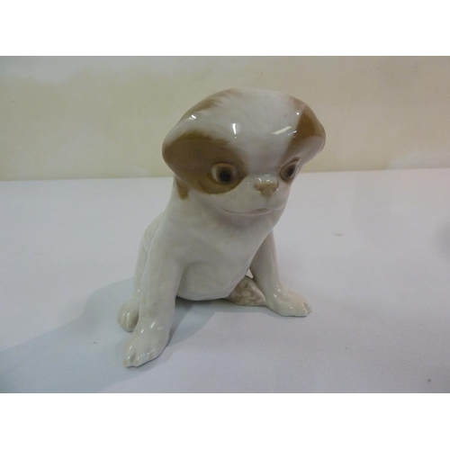 153 - Royal Copenhagen figurine of a seated dog, designed by Erik Nielsen, marks to the base, 14cm (h)...