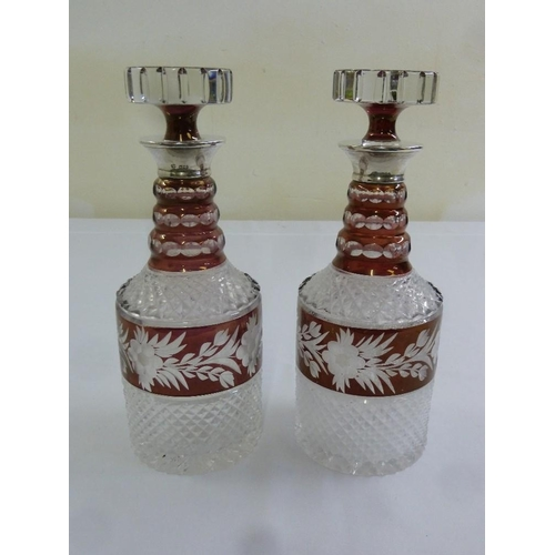 161 - A pair of overlaid cut glass decanters with drop stoppers and silver collars, A/F...