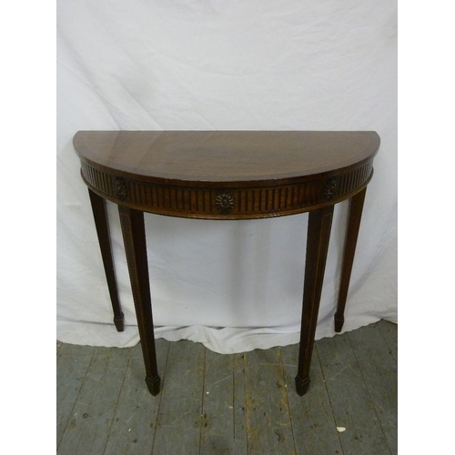 17 - A mahogany demilune hall table on four tapering rectangular legs...