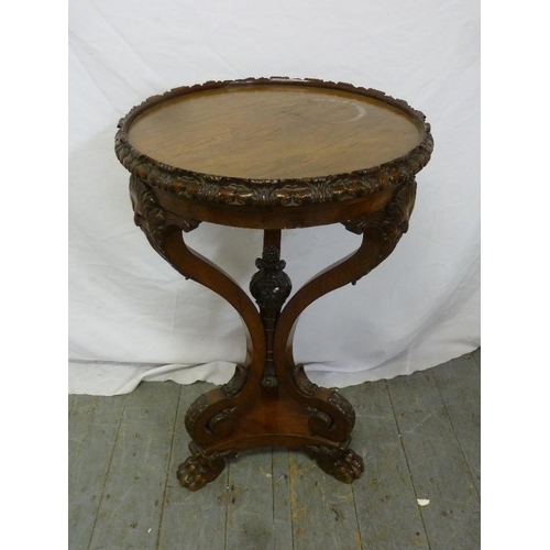 18 - A Continental mahogany occasional table, circular, masked mounted scroll supports on three scrolling...