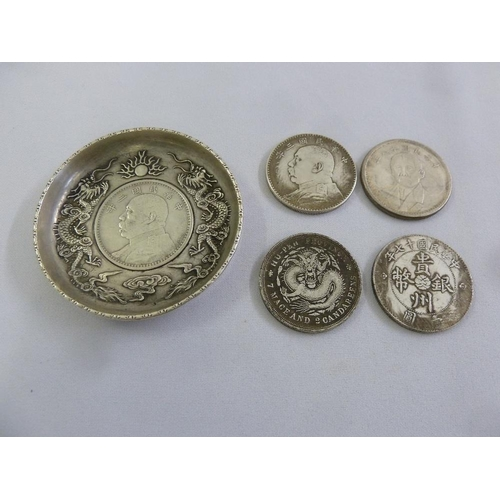 182 - A Chinese white metal pin tray set with a coin and four Chinese coins...
