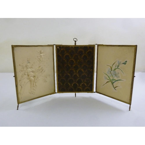199 - An early 20th century triptych folding brass frame mirror with central loop handle on three peg feet...