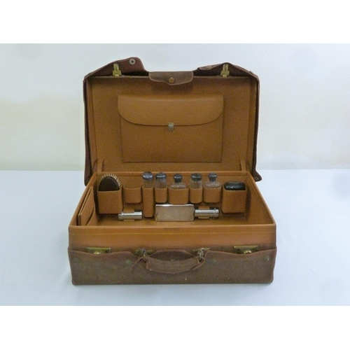 207 - A Mappin and Webb leather case fitted with silver topped bottles, hallmarked for London 1923, with o...
