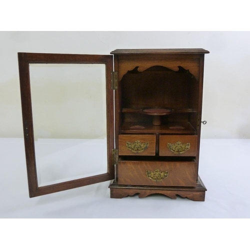 209 - A mahogany pipe cabinet of rectangular form with hinged glazed door with three drawers, to include k...