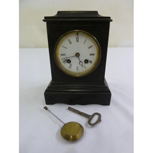 266 - A black slate mantle clock enamel dial, Roman numerals, two train movement to include key and pendul...
