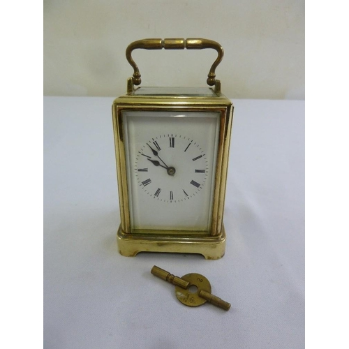 273 - A brass carriage clock of customary form, to include key...
