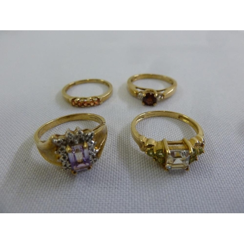 304 - Four 9ct gold rings set with various coloured stones...