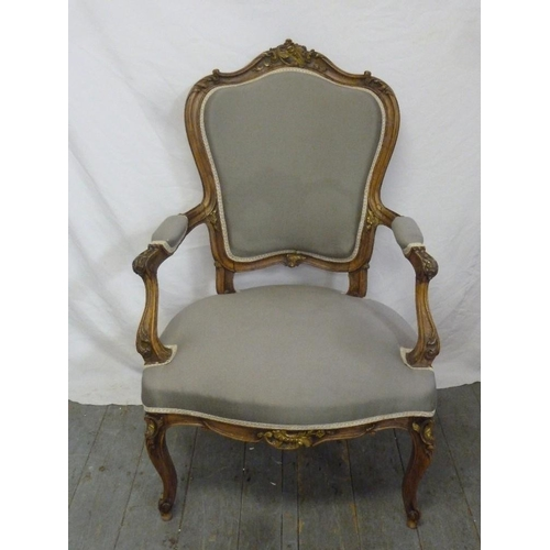 34 - An early 20th century upholstered armchair on cabriole legs...
