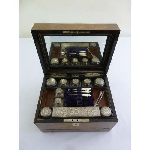 349 - A Victorian walnut travel boudoir set with silver covers to glass containers and mother of pearl man...