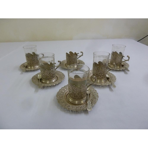 354 - A quantity of Persian white metal to include six tea glass holders, five glasses, six plates and six...