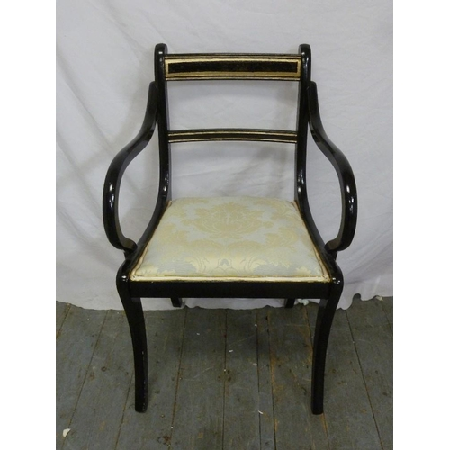 36 - An Edwardian ebonised armchair with upholstered seat on four sabre legs...