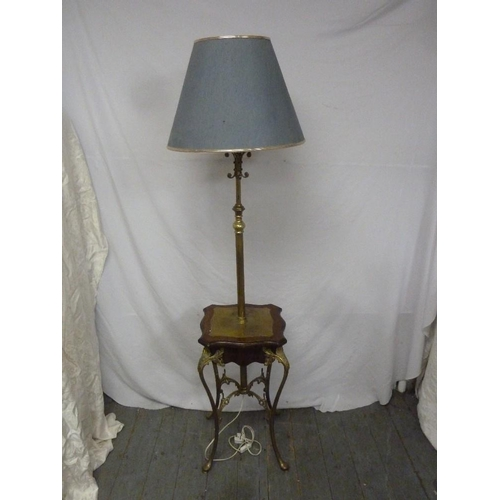 38 - A brass standard lamp with mahogany and brass mounts to the base with four scroll legs with shade...