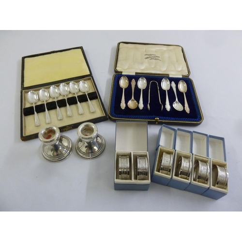 389 - A quantity of silver to include six napkin rings, two cased sets of tea spoons and a pair of dwarf c...