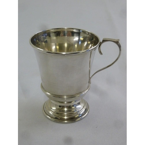 396 - A silver mug with scroll handle on raised circular base, Birmingham 1931...