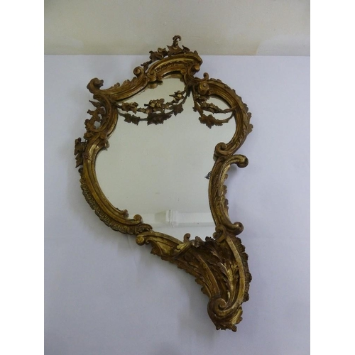 51 - A Continental gilt wood and gesso wall mirror in Rococo style...