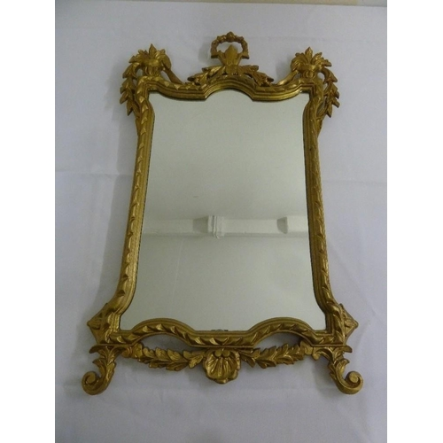 53 - A gilded rectangular wall mirror carved with leaves and scrolls in the French 19th century style...