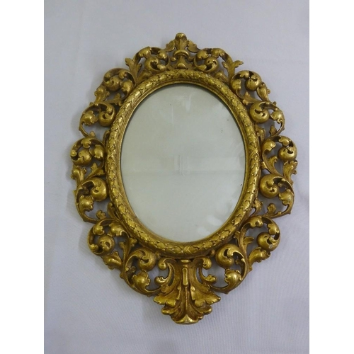 54 - An oval gilt wall mirror pierced and carved with leaves and scrolls...