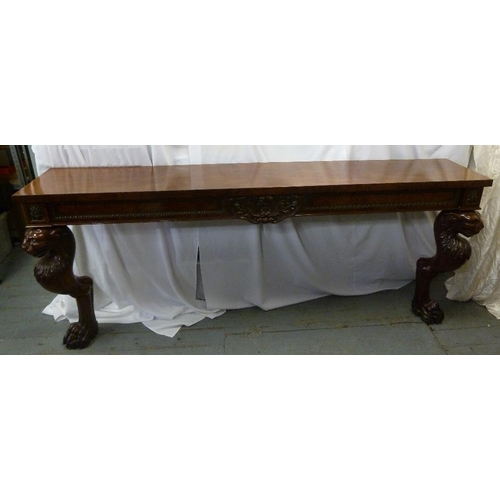9 - A French Empire mahogany consol table, rectangular with two stylised lion supports...
