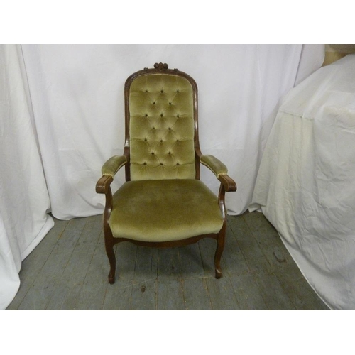 10 - A Victorian mahogany upholstered ladies button back armchair on four cabriole legs...