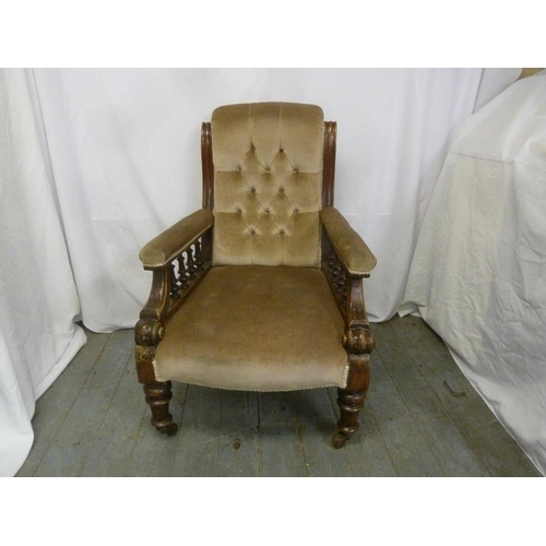 11 - A Victorian mahogany upholstered button back armchair with galleried sides on four turned legs...