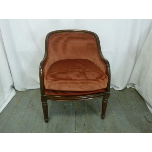 15 - A mahogany upholstered occasional chair on turned tubular legs...