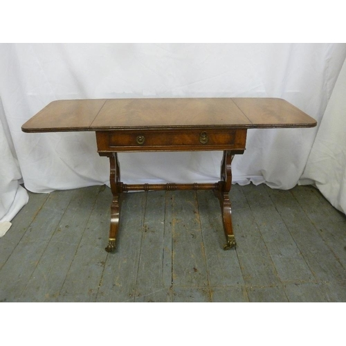 28 - A mahogany rectangular occasional table with hinged side flaps on scroll supports with original cast...