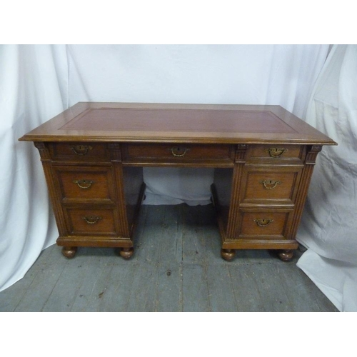 4 - A rectangular mahogany partners desk with tooled leather top, the nine drawers with brass swing hand...