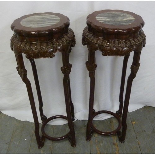 12 - A pair of Chinese hardwood plant stands with circular inset marble tops on four carved supports...