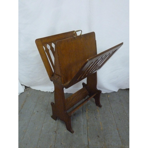 21 - An arts and crafts oak magazine rack of rectangular form with pierced sides on bracket supports...