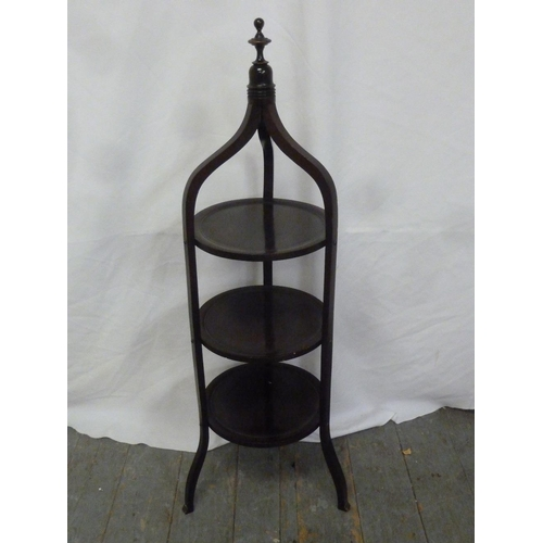 23 - Mahogany three tier plate stand surmounted by a carved finial...